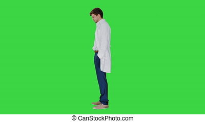 Sad male doctor giving bad news and shaking his head on a Green Screen, Chroma Key.