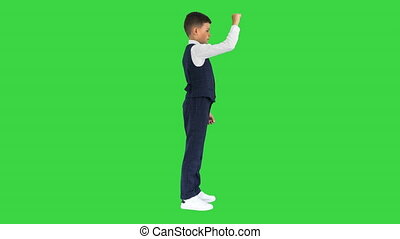 Wide shot. Side view. Schoolboy in a bow tie touching virtual screen on a Green Screen, Chroma Key. Professional shot in 4K resolution. 060. You can use it e.g. in your medical, commercial video, business, presentation, broadcast