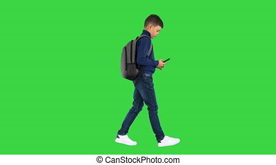 Wide shot. Side view. Schoolboy with a backpack texting on mobile phone while walking on a Green Screen, Chroma Key. Professional shot in 4K resolution. 060. You can use it e.g. in your medical, commercial video, business, presentation, broadcast