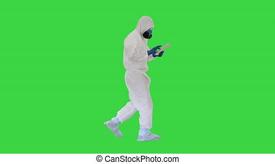 Scientist or docrot wearing biohazard suits and protective masks using digital tablet while walking on a Green Screen, Chroma Key.
