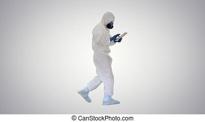 Wide shot. Side view. Scientist or docrot wearing biohazard suits and protective masks using digital tablet while walking on gradient background. Professional shot in 4K resolution. 53. You can use it e.g. in your medical, commercial video, business, presentation, broadcast