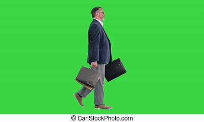Wide shot. Side view. Senior business man walking with shopping bag on a Green Screen, Chroma Key. Professional shot in 4K resolution. 059. You can use it e.g. in your medical, commercial video, business, presentation, broadcast