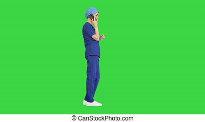 Serious female doctor talking on the phone on a Green Screen, Chroma Key.