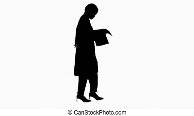 Silhouette Afro american doctor woman walking and looking at cardiogram record.