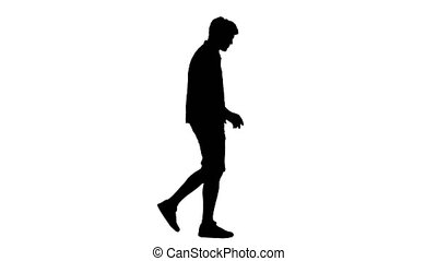 Wide shot. Side view. Silhouette Casual young man listening to music in headphones while walking. Professional shot in 4K resolution. 047. You can use it e.g. in your medical, commercial video, business, presentation, broadcast