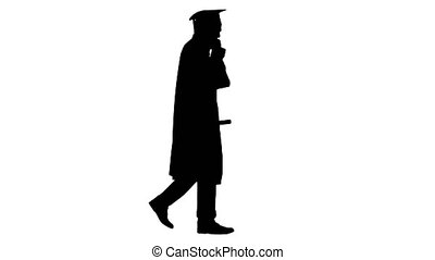 Wide shot. Side view. Silhouette Smiling male student in graduation robe walking and making a call. Professional shot in 4K resolution. 047. You can use it e.g. in your medical, commercial video, business, presentation, broadcast