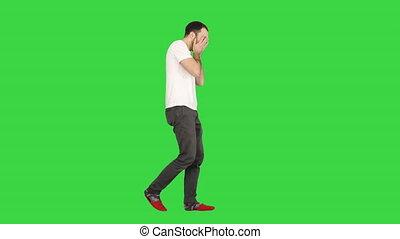 Sleepy man yawning and walking on a Green Screen, Chroma Key.