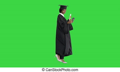 Wide shot. Side view. Smiling African American female graduate making selfie with diploma on a Green Screen, Chroma Key. Professional shot in 4K resolution. 046. You can use it e.g. in your medical, commercial video, business, presentation, broadcast
