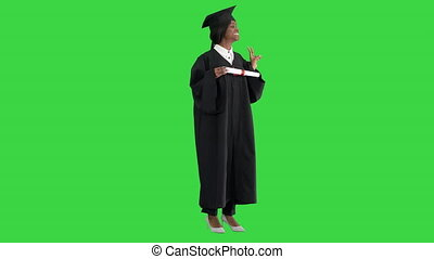 Wide shot. Side view. Smiling African American female student in graduation robe posing with diploma on a Green Screen, Chroma Key. Professional shot in 4K resolution. 046. You can use it e.g. in your medical, commercial video, business, presentation, broadcast