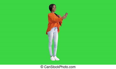 Wide shot. Side view. Smiling african american woman in bright jumper taking selfie and checking her phone on a Green Screen, Chroma Key. Professional shot in 4K resolution. 046. You can use it e.g. in your medical, commercial video, business, presentation, broadcast