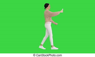 Wide shot. Side view. Smiling and gesturing young woman having video call on her phone while walking on a Green Screen, Chroma Key. Professional shot in 4K resolution. 043. You can use it e.g. in your medical, commercial video, business, presentation, broadcast