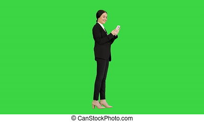 Wide shot. Side view. Smiling Businesswoman checking photos on her phone on a Green Screen, Chroma Key. Professional shot in 4K resolution. 043. You can use it e.g. in your medical, commercial video, business, presentation, broadcast