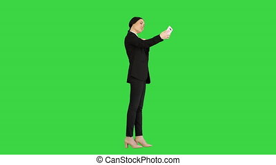 Wide shot. Side view. Smiling Businesswoman taking selfie on her phone on a Green Screen, Chroma Key. Professional shot in 4K resolution. 043. You can use it e.g. in your medical, commercial video, business, presentation, broadcast