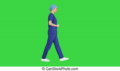 Smiling female in blue medical uniform advertising clinic services while walking on a Green Screen, Chroma Key.