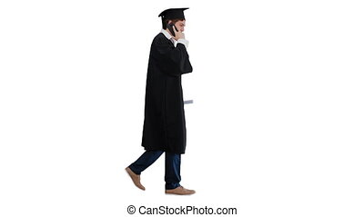 Wide shot. Side view. Smiling male student in graduation robe walking and making a call on white background. Professional shot in 4K resolution. 047. You can use it e.g. in your medical, commercial video, business, presentation, broadcast