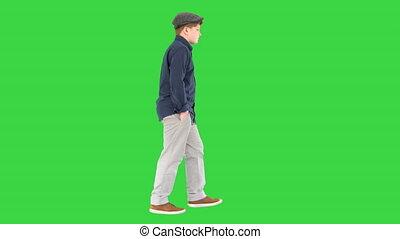 Stylish teenage boy in a shirt and a cap walking on a Green Screen, Chroma Key.