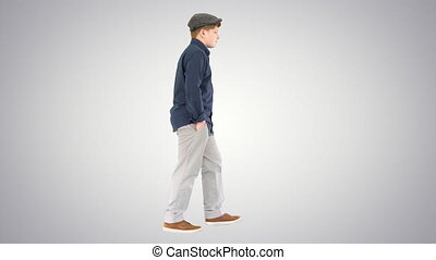 Stylish teenage boy in a shirt and a cap walking on gradient background.