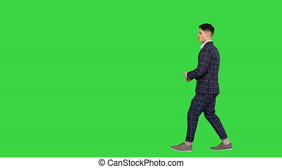 Wide shot. Side view. Walking in and out of the frame. Cool man in formal outfit walking and dancing on a Green Screen, Chroma Key. Professional shot in 4K resolution. 022. You can use it e.g. in your commercial video, business, presentation, broadcast