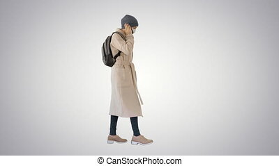 Woman wearing medical mask walking and calling someone one the phone on gradient background.