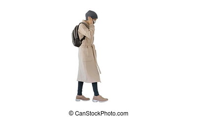 Woman wearing medical mask walking and calling someone one the phone on white background.