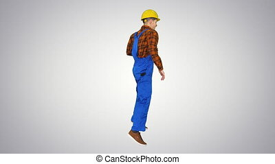 Young construction worker in hard hat dancing hip-hop on ...