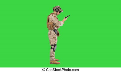 Wide shot. Side view. Young man in military uniform checking revolver gun on a Green Screen, Chroma Key. Professional shot in 4K resolution. 048. You can use it e.g. in your medical, commercial video, business, presentation, broadcast