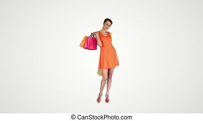 Beautiful girl shows bags with purchases turning around on gradient background.
