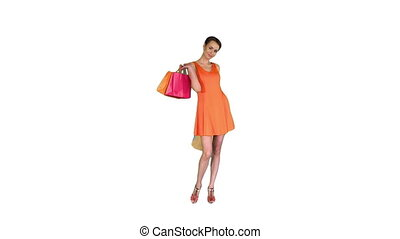 Beautiful girl shows bags with purchases turning around on white background.