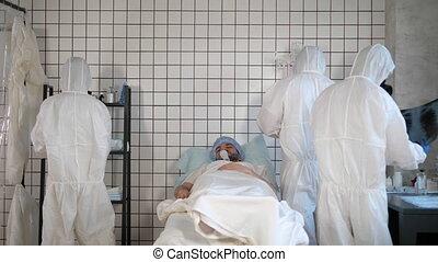 Doctors in Hazmat Sterile Suit around the patient in a hospital.