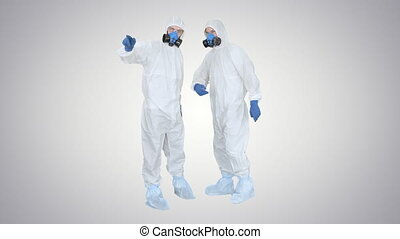 Wide shot. Three men in protective uniform enter the frame one after another. Disinfection needed Doctor in protective uniform calls his colleagues for help on gradient background. Professional shot in 4K resolution. 53. You can use it e.g. in your medical, commercial video, business, presentation, ...