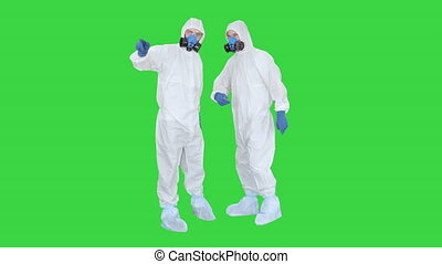 Wide shot. Three men in protective uniform enter the frame one after another. Disinfection needed Doctor in protective uniform calls his colleagues for help on a Green Screen, Chroma Key. Professional shot in 4K resolution. 53. You can use it e.g. in your medical, commercial video, business, ...