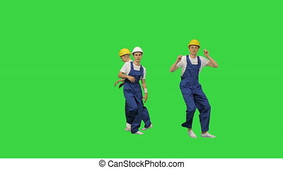 Group of builders walk in the frame and dance on a Green Screen, Chroma Key.