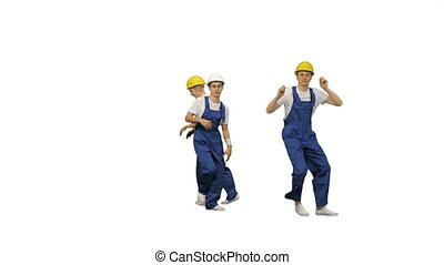 Group of builders walk in the frame and dance on white background.
