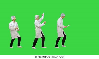 Wide shot. Walk in and out of the frame. Male medicine doctor checking something at his papers Medical care, insurance, prescription, paper work or career concept Physician ready to examine patient and help on a Green Screen, Chroma Key. Professional shot in 4K resolution. 4151. You can use it e.g. ...