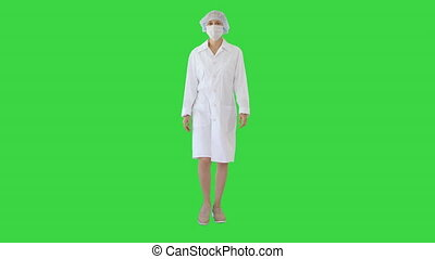 Walking female doctor wearing surgical mask on a Green Screen, Chroma Key.
