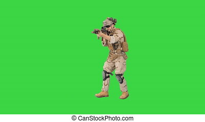 Wide shot. Walking in and out of the frame. Armed marine soldier with assault rifle walking by aiming on a Green Screen, Chroma Key. Professional shot in 4K resolution. 048. You can use it e.g. in your medical, commercial video, business, presentation, broadcast