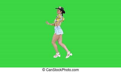 Cowboy girl dances walking on a Green Screen, Chroma Key. -...