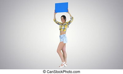 Wide shot. Walking in and out of the frame. Girl with an empty board announcing new round on gradient background. Professional shot in 4K resolution. 021. You can use it e.g. in your commercial video, business, presentation, broadcast