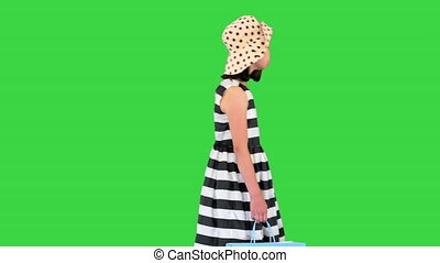 Wide shot. Walking in and out of the frame. Little girl in sundress walking by with skateboard in her hands on a Green Screen, Chroma Key. Professional shot in 4K resolution. 062. You can use it e.g. in your medical, commercial video, business, presentation, broadcast
