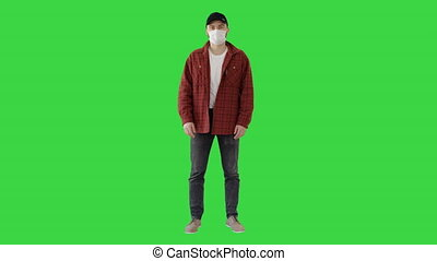 Wide shot. Young Man Gesturing And Wearing Mask Showing Thumb Up on a Green Screen, Chroma Key. Professional shot in 4K resolution. 53. You can use it e.g. in your medical, commercial video, business, presentation, broadcast