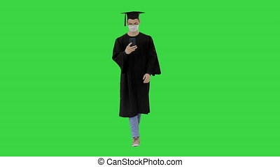 Young man with graduation gown walking in medical mask using smartphone on a Green Screen, Chroma Key.