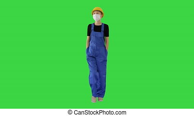 Wide shot. Young woman in yellow hardhat and in medical mask walking on a Green Screen, Chroma Key. Professional shot in 4K resolution. 53. You can use it e.g. in your medical, commercial video, business, presentation, broadcast