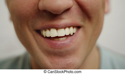 Wide sincere smile of a young man, close up, positive emotions