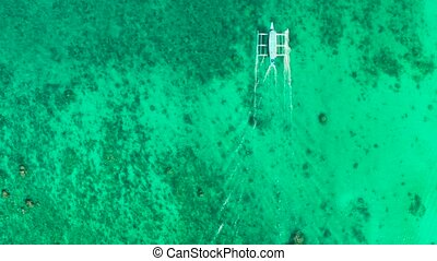 Sea water surface in lagoon with motor boat, copy space for text, aerial view. Top view transparent turquoise ocean water surface. background texture