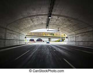 Wide tunnel on a freeway with moving cars