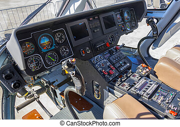 Wide view, a cockpit of a small helicopter, a control panel and a steering wheel.