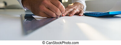 Wide view image of an architect drawing a line along a ruler