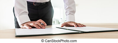 Wide view image of business executive about to sign a document