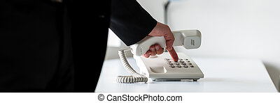Wide view image of businessman dialing telephone number -...