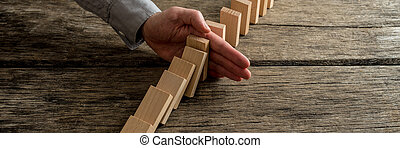 Wide view image of businessman stopping domino effect